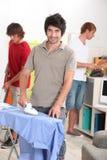Tres hombres que hacen el quehacer doméstico Foto de archivo libre de regalías