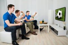 Tres hombres que miran el partido de fútbol Imagenes de archivo