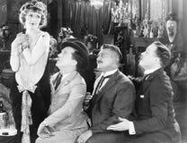 Tres hombres que miran vehementemente una mujer (todas las personas representadas no son vivas más largo y ningún estado existe T Imagen de archivo libre de regalías