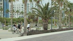 Tres hombres que montan las bicicletas en el parque almacen de video