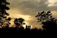 Tres hombres que recorren en cielo de la puesta del sol Fotografía de archivo