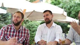 Tres hombres que se sientan en café, cerveza de consumición y haciendo la foto de la multitud almacen de video