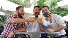 Tres hombres que se sientan en café, cerveza de consumición y haciendo la foto por el teléfono almacen de metraje de vídeo