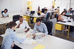 Tres hombres que trabajan junto en una oficina ocupada, visión elevada fotografía de archivo libre de regalías