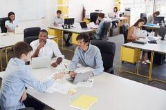 Tres hombres que trabajan junto en una oficina ocupada, visión elevada fotos de archivo