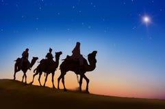 Tres hombres sabios que montan el camello en la colina Foto de archivo libre de regalías