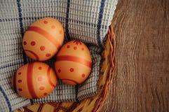 Tres huevos adornados Pascua en una cesta Imágenes de archivo libres de regalías