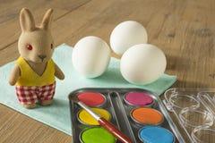 Tres huevos blancos con la pintura, el cepillo y el conejito de pascua fotos de archivo libres de regalías