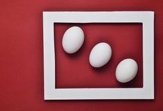 Tres huevos blancos del pollo en un marco blanco en un fondo rojo Tendencia minimalista Foto de archivo libre de regalías
