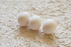 tres huevos blancos en fondo blanco texturizado Fotos de archivo libres de regalías