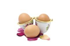 Tres huevos con los pétalos Imagen de archivo