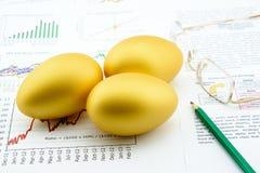 Tres huevos de oro con un lápiz y los vidrios del ojo sobre negocio e informes resumidos financieros imágenes de archivo libres de regalías