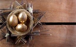 Tres huevos de oro en una jerarquía Fotos de archivo libres de regalías