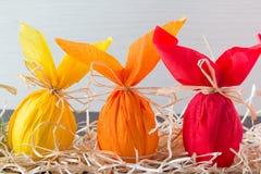 Tres huevos de Pascua coloridos bajo la forma de conejo en fondo marrón claro Adornamiento del día de fiesta Imagenes de archivo
