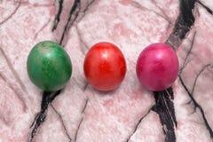 Tres huevos de Pascua coloridos brillantes Huevos de Pascua rosados, amarillos, verdes en fondo desigual azul en el fondo blanco Fotografía de archivo libre de regalías
