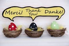 Tres huevos de Pascua coloridos con el globo de discurso cómico con agradecen le en francés-inglés y alemán Foto de archivo