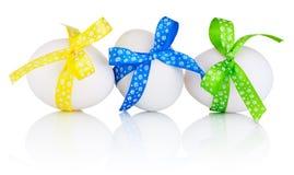 Tres huevos de Pascua con el arco festivo aislado en el fondo blanco foto de archivo
