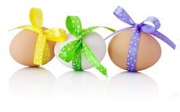 Tres huevos de Pascua con el arco festivo aislado en el fondo blanco Fotos de archivo