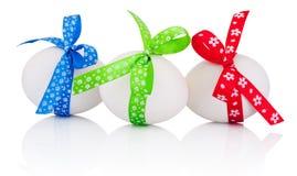 Tres huevos de Pascua con el arco festivo aislado en un fondo blanco fotos de archivo libres de regalías