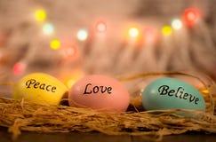 Tres huevos de Pascua en cama de la paja con palabras fotos de archivo
