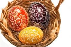 Tres huevos de Pascua en cesta tejida Fotografía de archivo