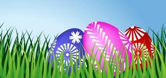 Tres huevos de Pascua en hierba Foto de archivo libre de regalías