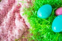 Tres huevos de Pascua en hierba plástica verde y fondo rosado Imagenes de archivo