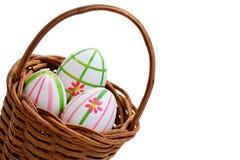 Tres huevos de Pascua en una cesta de la esquina Fotos de archivo