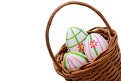 Tres huevos de Pascua en una cesta de la esquina Imagenes de archivo