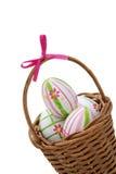 Tres huevos de Pascua en una cesta de la esquina Foto de archivo