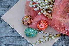 Tres huevos de Pascua entre el sauce en la textura de papel Imagenes de archivo