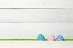 Tres huevos de Pascua hechos a mano coloridos se colocan en un césped verde, cubierto con una barrera, en un fondo de madera blan Foto de archivo libre de regalías
