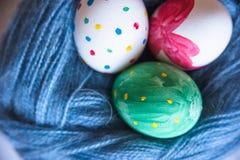 Tres huevos de Pascua mienten en un enredo de lanas Imágenes de archivo libres de regalías