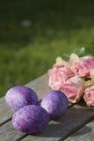 Tres huevos de Pascua púrpuras con las rosas Foto de archivo libre de regalías