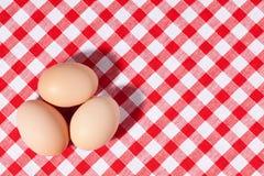 Tres huevos en mantel de la comida campestre Imagen de archivo libre de regalías