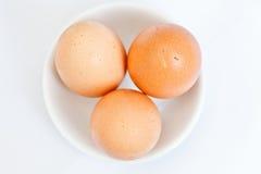 Tres huevos en un pequeño platillo blanco Fotos de archivo libres de regalías