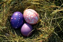 Tres huevos multicolores en heno imagen de archivo