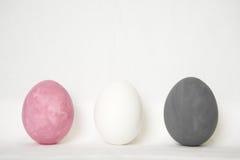 Tres huevos rosados grises blancos de pascua Imagen de archivo libre de regalías