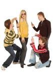 Tres individuos hacen la foto de una muchacha por un móvil fotografía de archivo