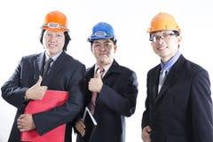 Tres ingenieros con el pulgar encima de la muestra Fotografía de archivo libre de regalías