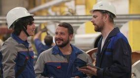 Tres ingenieros de los amigos en la fábrica de la industria pesada, sonrisa y discuten planes