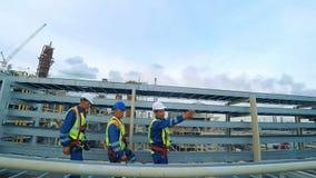 Tres ingenieros en el casco de protección se están moviendo a través de una fábrica de la industria pesada almacen de metraje de vídeo