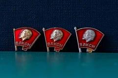 Tres insignias de Komsomol del soviet en un fondo del verde azul Fotos de archivo