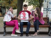 Tres jóvenes, adolescentes, un masculino caucásico y dos hembras, comiendo la pizza y sentarse sonriente en un banco en Lviv cént Imágenes de archivo libres de regalías