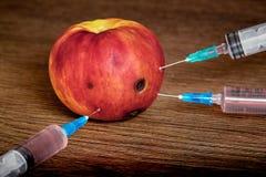 Tres jeringuillas se insertan en la manzana con los rastros de la putrefacción Adopción de drogas El problema de la drogadicción  imagen de archivo