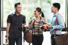 Tres jovenes y empleados alegres en su lugar de trabajo que hablan por la mañana imagen de archivo libre de regalías