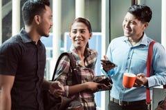 Tres jovenes y empleados alegres en su lugar de trabajo que hablan por la mañana imagenes de archivo