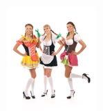 Tres jovenes y mujeres felices en ropa bávara foto de archivo