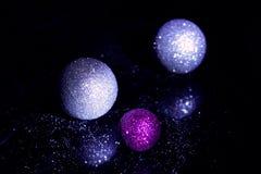 Tres juguetes brillantes del árbol de navidad sobre un vidrio negro Fotos de archivo