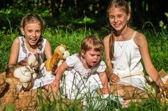 Tres juguetes del juego de las hermanas en parque imagenes de archivo